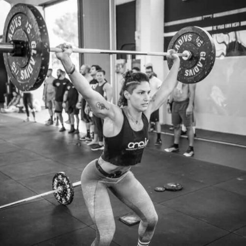 female athlete lifting the barbell crossfit program