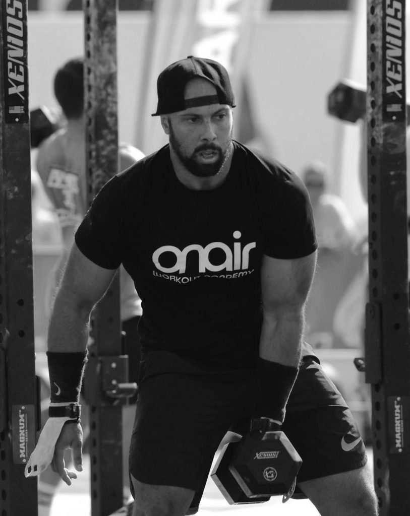 crossfit athlete hanging a dumbell